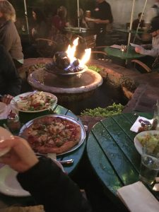 A close up of an arm and pizza on a table with a decorative fountain lit with fire at the top